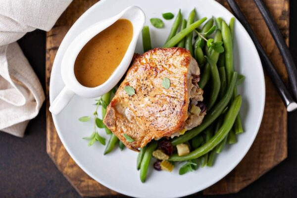 Cranberry apple stuffed pork chops sitting on top of green beans with pan gravy in a gravy boat.