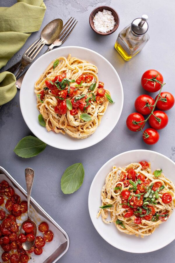 Creamy Pasta with Roasted Cherry Tomatoes in two white bowls surrounded by ingredients