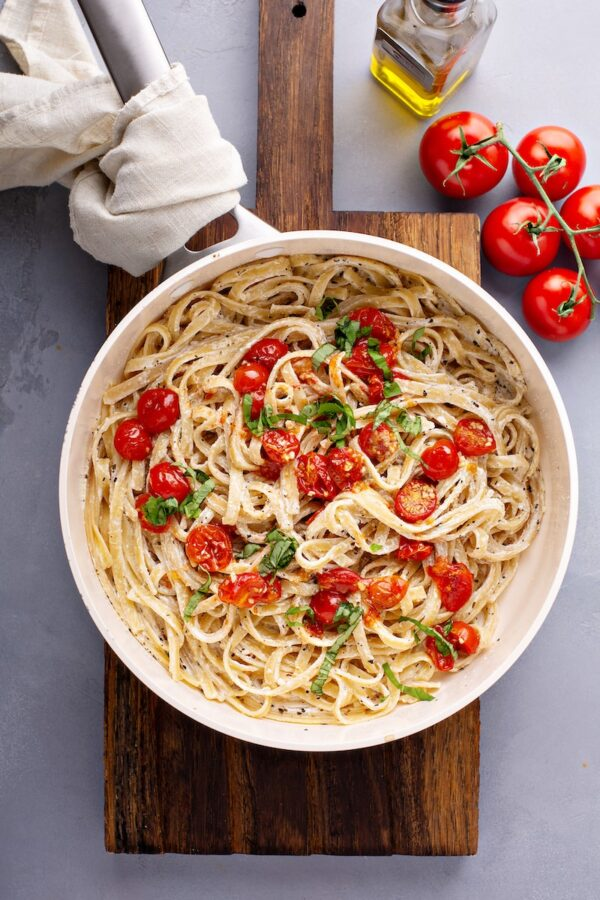 Creamy goat cheese pasta in a pan topped with roasted garlic cherry tomatoes and fresh basil