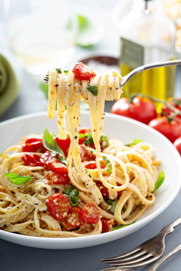 A fork with creamy fettuccine on it over a bowl of more pasta and tomatoes