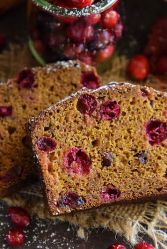 Two slices of pumpkin cranberry buttermilk bread with fresh cranberries