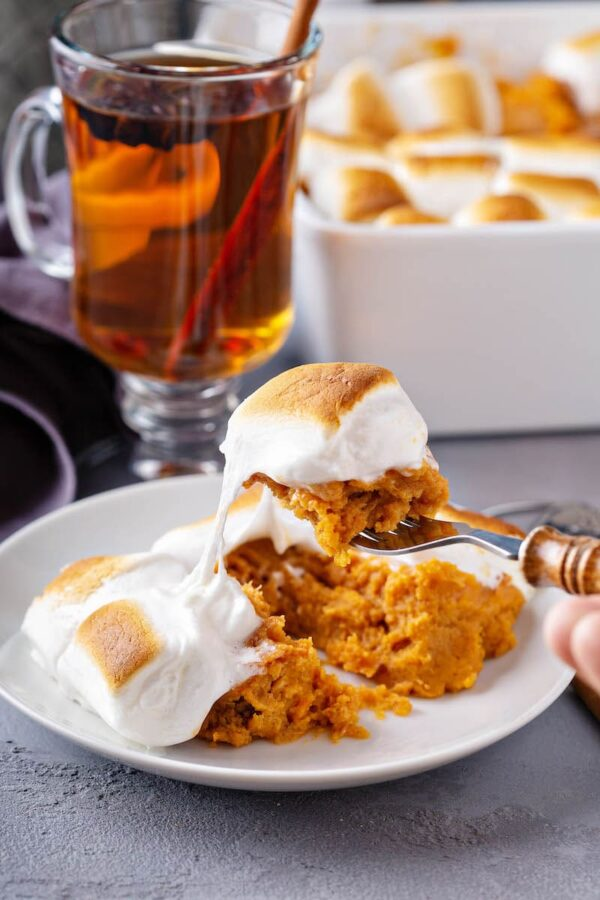 A fork taking a scoop of sweet potato casserole and a toasted marshmallow from a white plate