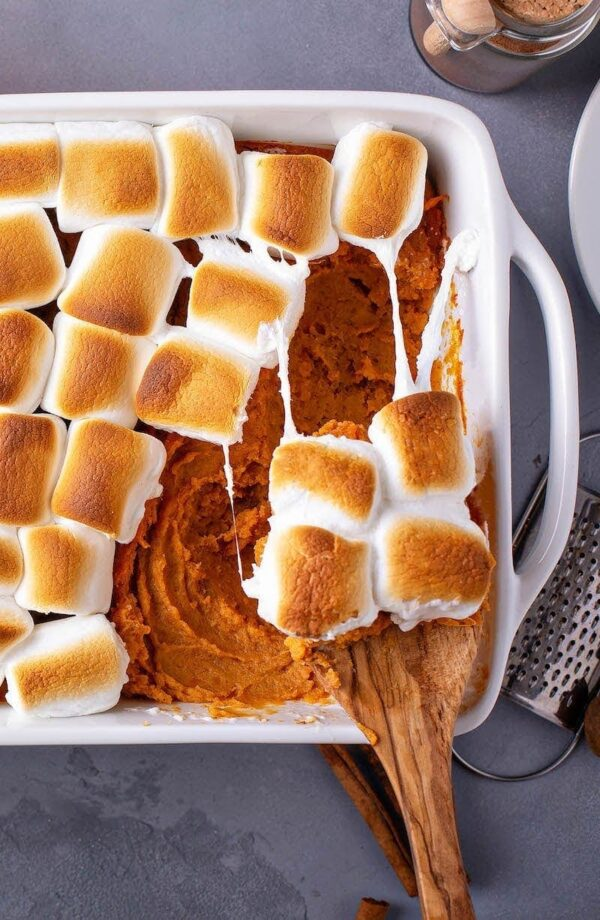 Sweet potato casserole marshmallows being scooped out of white casserole dish.