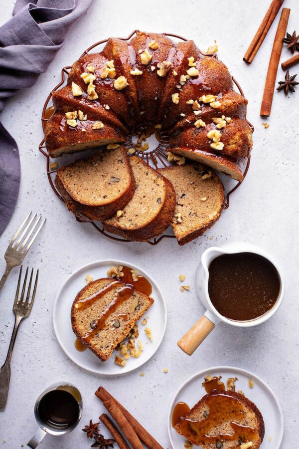 Walnut Rum Bundt Cake sliced on cake plate with a slice of rum cake on a small plate drizzled with rum sauce.