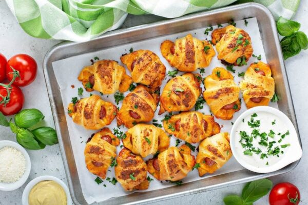 Cheesy Ranch Pigs In A Blanket on a baking sheet with ranch dressing for dipping.