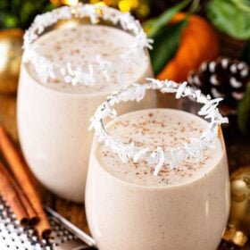 Two glasses of coquito with cinnamon on top.