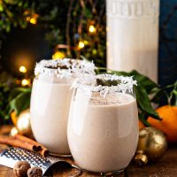 Coquito in two glasses with large jar behind.