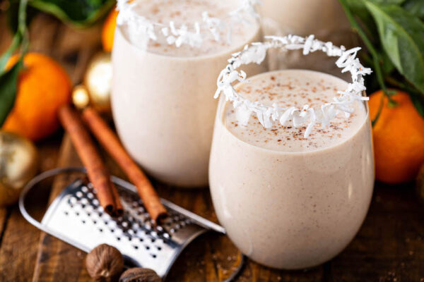 Coquito in two glasses with coconut rims and ground cinnamon.