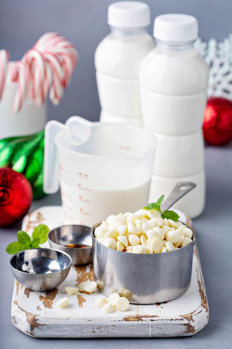 White Chocolate Chips, Half and Half, Vanilla Extract and the Rest of the Christmas Hot Cocoa Ingredients on a Cutting Board