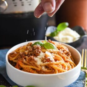 Spaghetti Bolognese in a bowl with fresh parmesan being sprinkled on top.