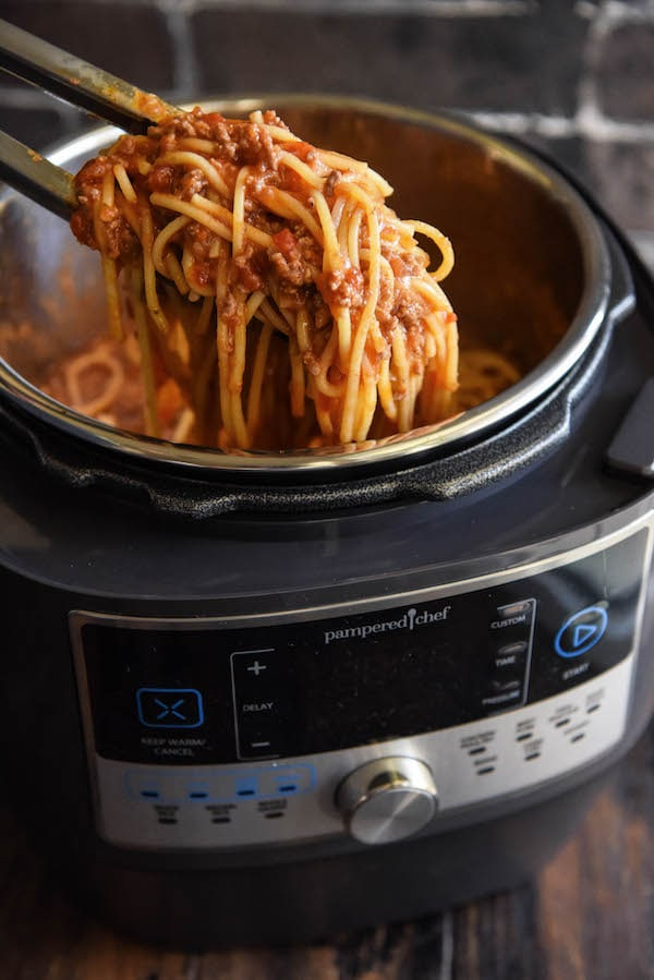 Spaghetti being pulled out of a quick cooker with tongs.