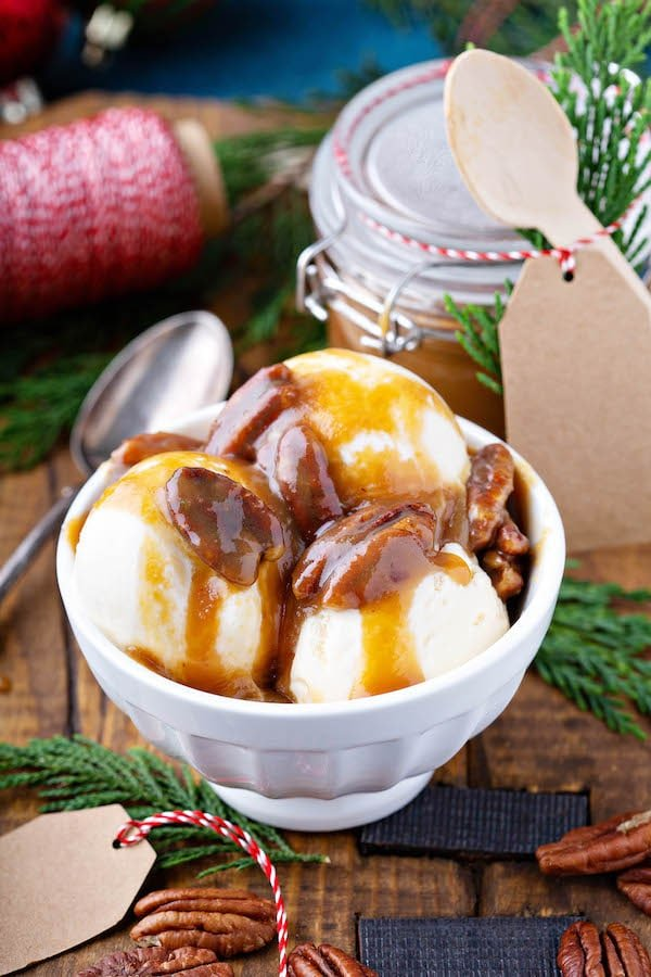 Pecan Praline Sauce in bowl poured over vanilla ice cream.