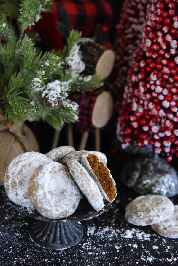 Pfeffernusse Cookies with powdered sugar sprinkled all around and Christmas trees in background.
