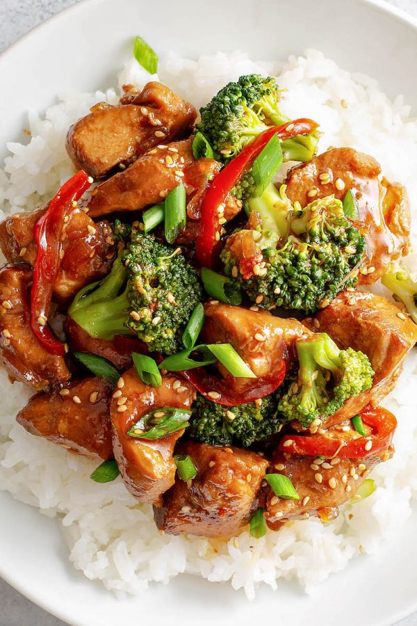 Sesame Chicken served over rice with broccoli.