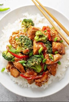 Crockpot Sesame Chicken with veggies and sesame seeds on a bed of rice on a white plate with chopsticks