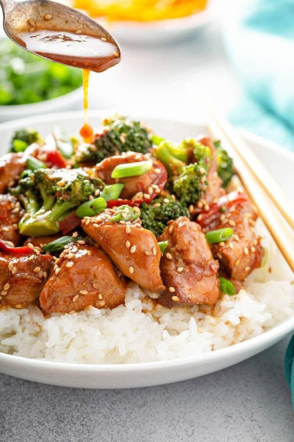 Close up shot of sesame chicken with broccoli served over white rice topped with green onions and sesame seeds.