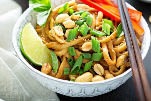Peanut noodles in a bowl topped with cilantro, peanuts and a lime wedge.