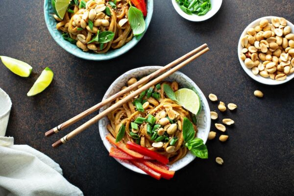 Spicy Peanut Noodles with cilantro, lime, and crushed peanuts on top.