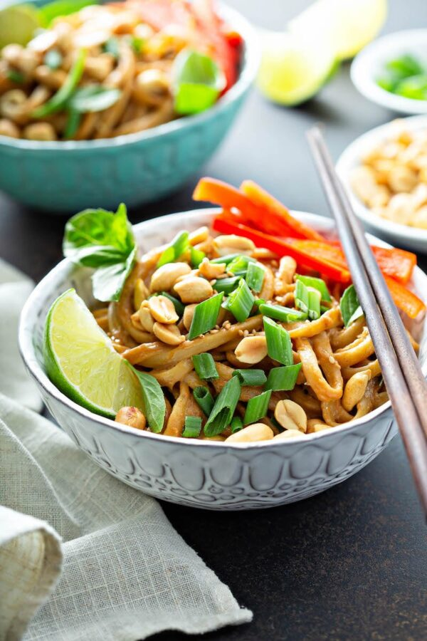 A quick 20 minute Spicy Peanut Noodles recipe with a spicy homemade peanut sauce that is tossed over noodles and topped with peanuts, green onions and lime. #SpicyPeanutNoodles #PeanutNoodles #Noodles #Thai #Takeout #Recipe #QuickDinner #EasyDinnerRecipes #DinnerRecipes #LunchIdeas