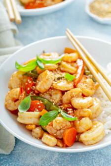 Teriyaki Shrimp StirFry in a bowl served over rice with sesame seeds sprinkled on top.