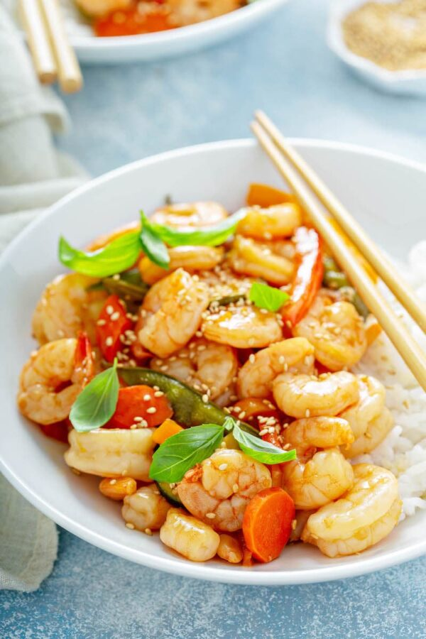 Teriyaki Shrimp StirFry in a bowl served over rice with sesame seeds sprinkled on top.