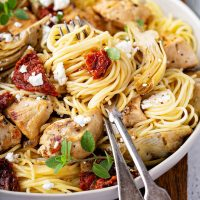 Pasta swirled in a plate with chicken, artichokes, sun dried tomatoes and goat cheese.