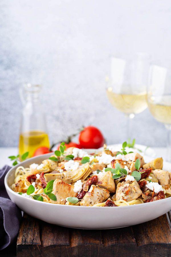 Chicken, Artichoke and Sun-Dried Tomato Pasta in a bowl with two glasses of white wine.