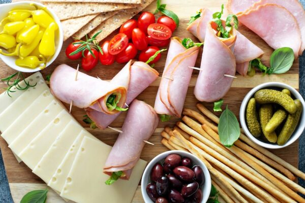 Ham Roll Ups on a platter with cheese, olives, tomatoes and more.