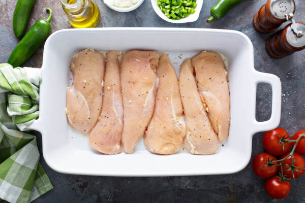 Chicken breasts in casserole dish with salt and pepper.
