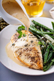 Sautéed chicken breast and green beans with a creamy lemon caper sauce being poured on top.