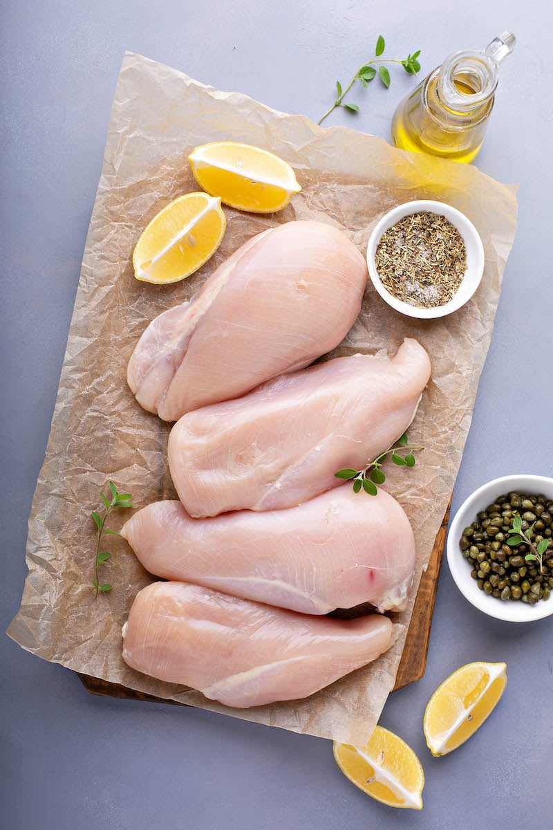 Chicken breasts on parchment paper with herbs and lemons and olive oil.