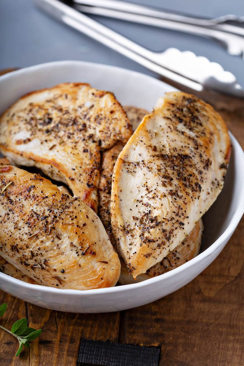 Sauteed seasoned chicken breasts in a skillet.
