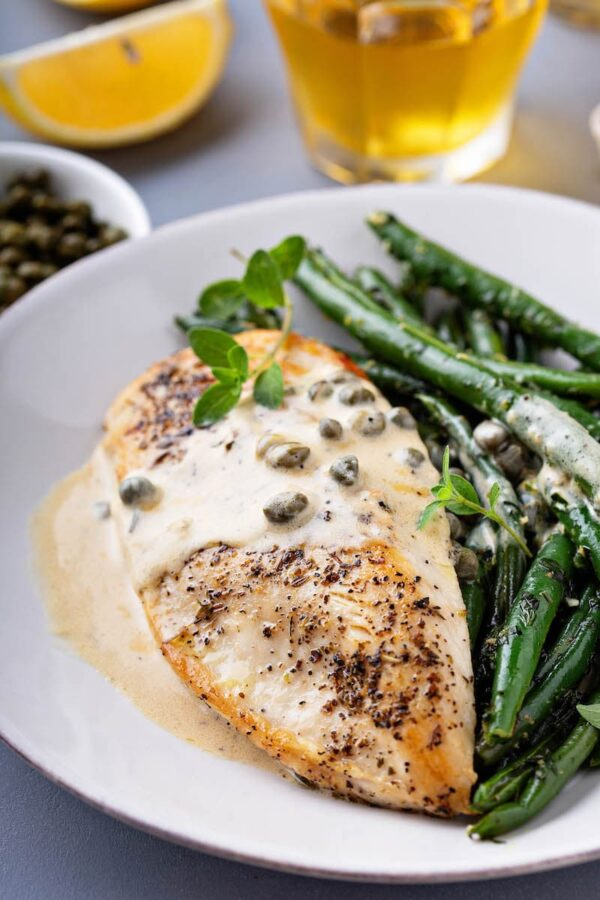 Browned chicken breasts with lemon caper sauce drizzled on top.