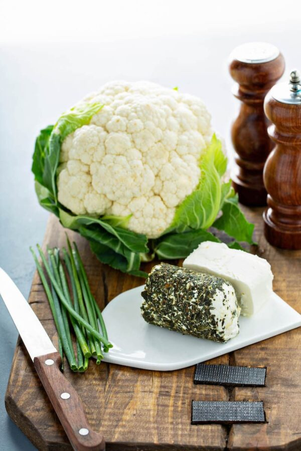 Cauliflower, herbed goat cheese, cream cheese and chives on a platter.
