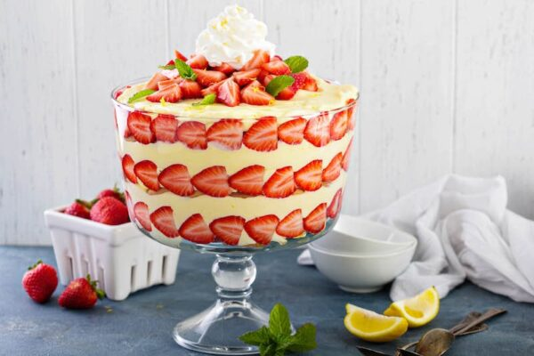 Large trifle bowl filled with lemon strawberry pudding trifle
