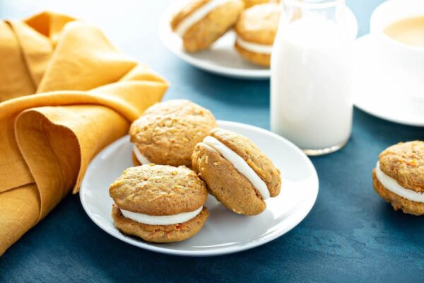 Carrot Cake Whoopie Pies on a plate with a glass of milk.