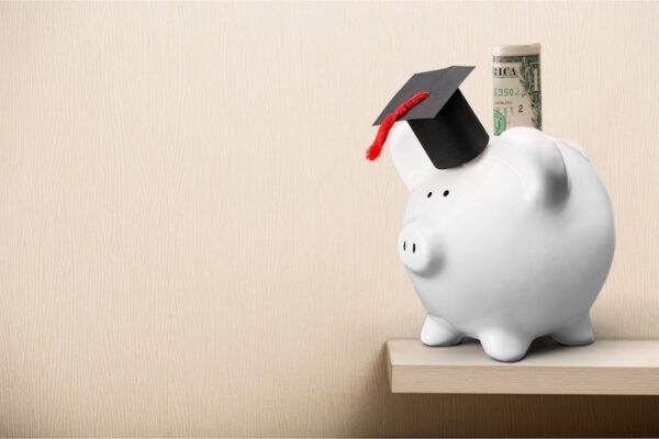 White piggy bank with a graduation hat on it.