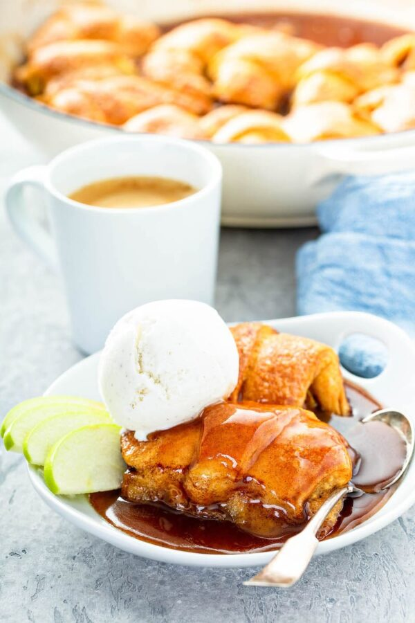 Rum Apple Dumplings served in a bowl with ice cream and sauce.