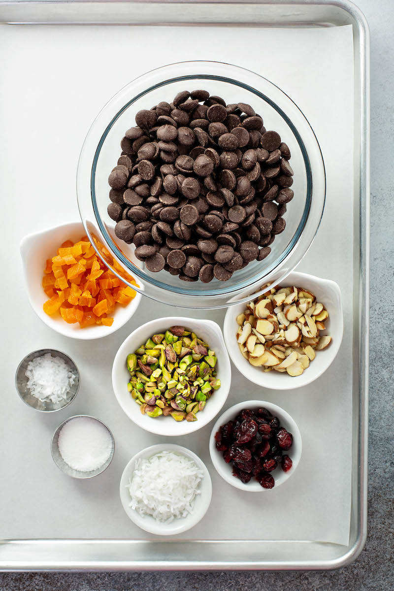 A Lined Baking Sheet Holding Bowls of Chocolate Chips, Coconut Flakes and the Remaining Bark Ingredients