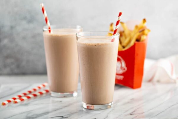 Two copycat wendy's chocolate frostys in glasses with fries.