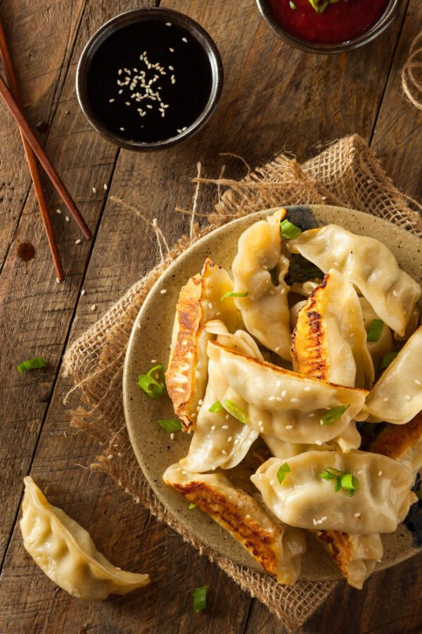 Potstickers on a plate with potsticker sauce in a small bowl with sesame seeds.