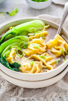 Wonton Soup in a bowl with bok choy and a spoon.
