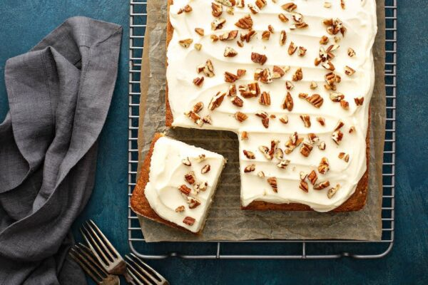 Banana Pecan Cake with cream cheese and pecans sprinkled on top.