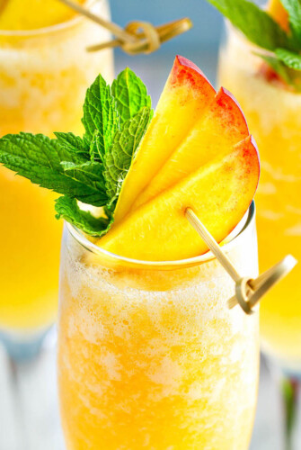 Up close image of peach bellini with fresh peaches and mint on top.