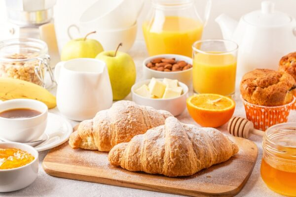 brunch recipe table filled with juices, fruits and croissants.
