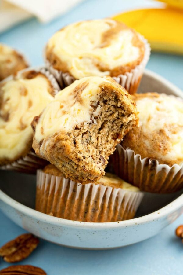 Banana Cream Cheese Muffins in a bowl with a bite taken out of one.