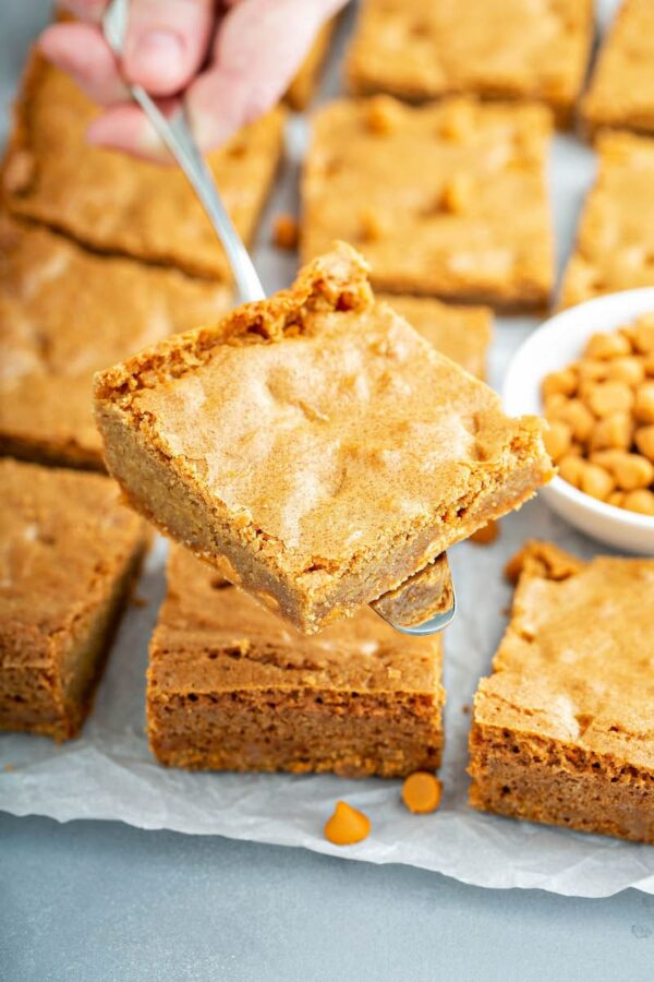 Butterscotch Blondies on parchment paper and one is being scooped up with a spatula.