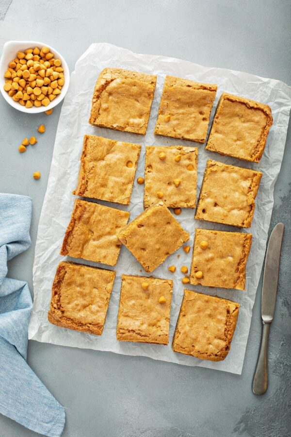 Butterscotch blondies sliced into squares on a parchment paper.