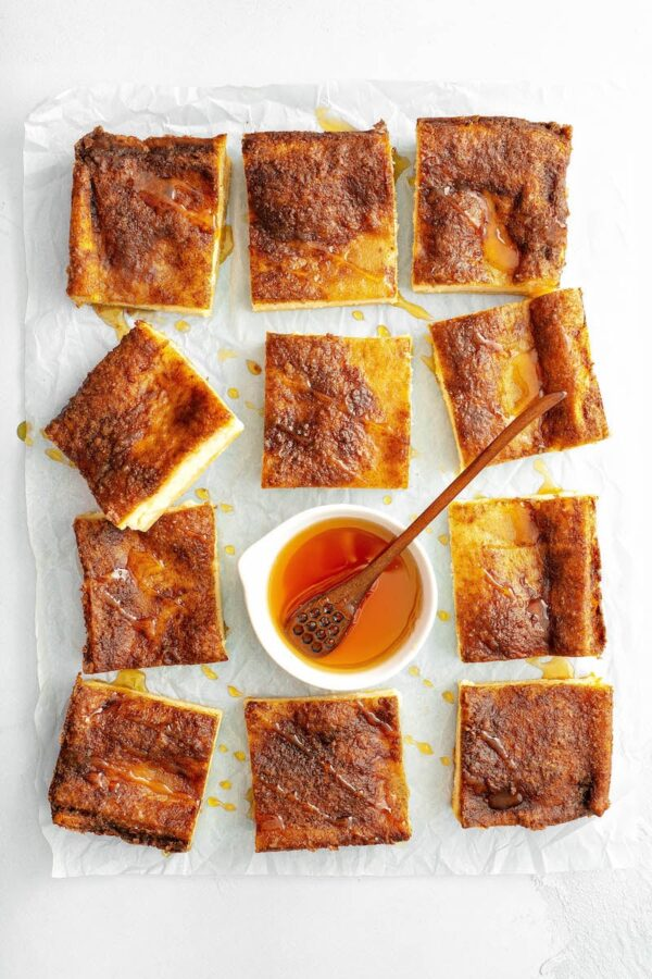 Sopapiall Cheesecake bars cut into squares on parchment paper.