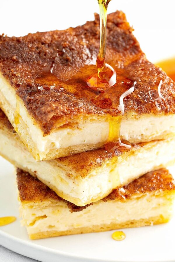 Sopapilla Cheesecake stacked on top of each other with a drizzle of honey.